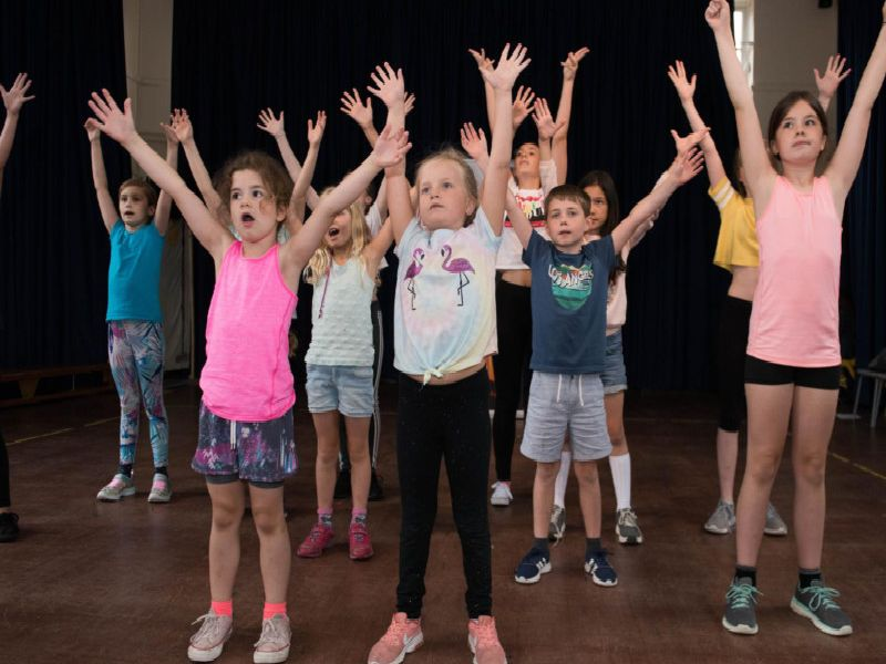 Stagecoach Buckingham's Millennials summer camp at The Buckingham School - pupils with their hands up in the air!