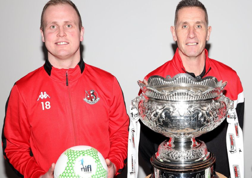 Crusaders striker Jordan Owens (left) and manager Stephen Baxter in front of the League Cup trophy. Pic by Pacemaker.