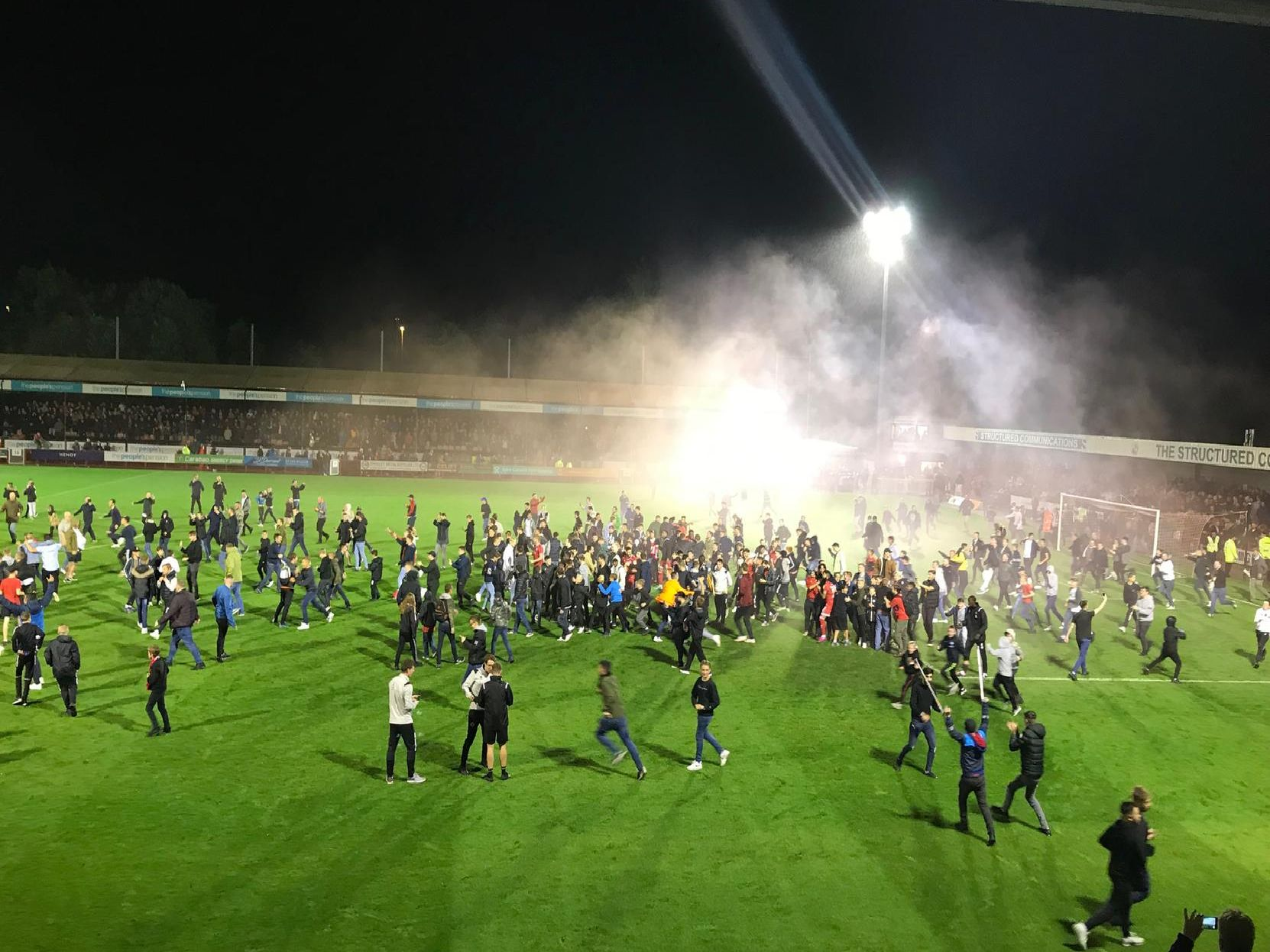 Crawley fans celebrate by invading the pitch after Ollie Palmer's winning penalty