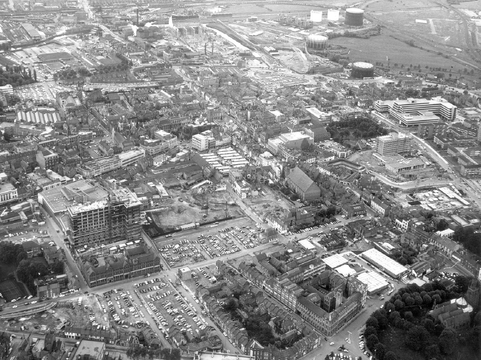 This aerial photograph of Northampton, taken in around 1972, reveals the extent of demolition that had taken place in the heart of the town leaving large swathes of car parking space: Ladys Lane runs from left to right (west to east). 'In the far right hand corner is The Church of the Holy Sepulchre, surrounded by trees: top middle is the modern Carlsberg Brewery.