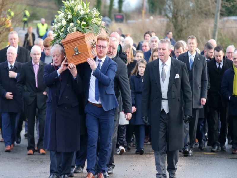 Mourners walk the final few steps carrying the coffin of Seamus Mallon into St James of Jerusalem Church in Mullaghbrack, Co. Armagh.