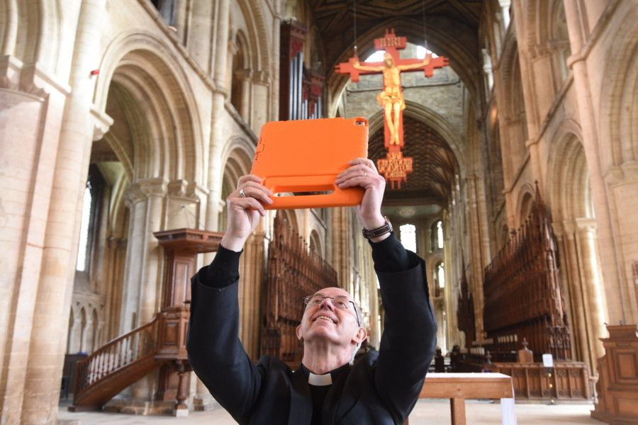 Archbishop of Cantebury  using the new Peterborough Cathedral app with local children. EMN-191004-144753009