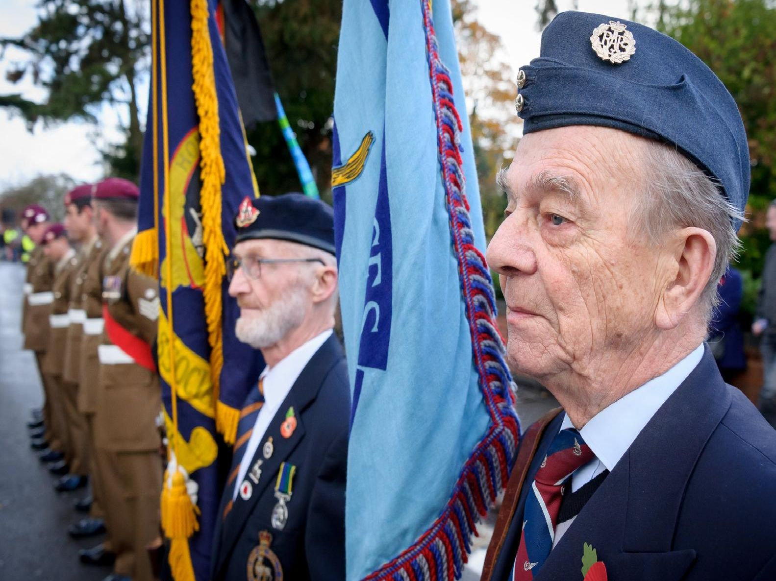 Two veterans stand alongside soldiers from the Parachute Regiment.