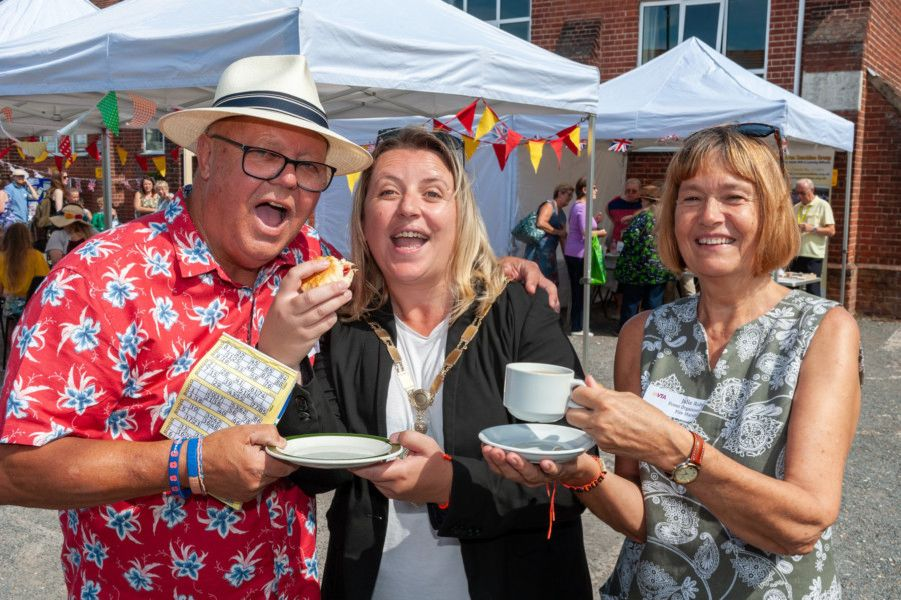 Wick, Littlehampton, West Sussex, UK. 24th August 2019. The Wick Festival Family Cream Tea event at Wick Hall. In Pic: The Mayor of Littlehampton, Councillor Tracey Baker, enjoys a scone with jam and cream and a cup of tea at the event with the event organisers Keith Croft and Julie Roby.