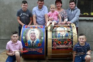 The Sterritt family ' from left, Jack, Luke, Jordan, Hollie, mum Kelley, Ethan and Charlie ' and their Lambegs with paintings of their late father Richard and grandfather Ernie on them. Picture: Ulster Gazette