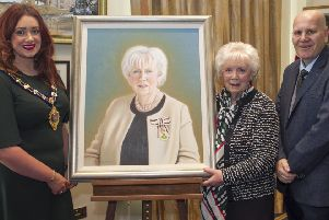 Joan Christie is presented with a portrait by the Mayor of Mid and East Antrim, Councillor Lindsay Millar and Councillor Paul Reid.