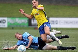 Institute's Graham Crown slides in and fouls Ballymena United midfielder Leroy Millar.