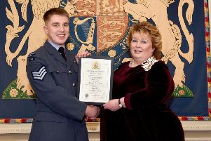 Mrs Fionnuala Jay-O'Boyle, Her Majesty's Lord Lieutenant for the County Borough of Belfast, presents Cadet Sergeant Ryan McDowell with the certificate which marks his latest achievement
