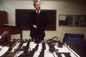 An RUC officer displays arms found in a drum under the kitchen of a Springfield Road house in west Belfast in 1987