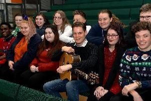 Singer songwriter Pete Gardiner (holding guitar) sits with Chenderit students before playing