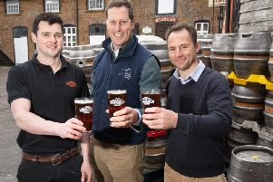 Cheers! Jamie OSullivan from Hook Norton Brewery, Charlie Longsdon and'Andre Klein with a pint of The Kingmaker Ale. Photo: Warwick Racecourse