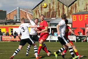 Banbury United's Charlie Wise is outnumbered against King's Lynn Town. Photo: Steve Prouse