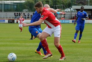 Brackley Town's Jimmy Armson turns FC United of Manchester's Chris Lynch. Photo: Jake McNulty