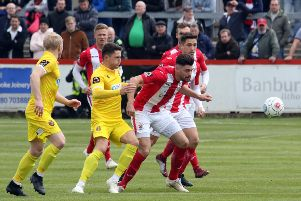 Brackley Town's Connor Hall beats Spennymoor Town's Jamie Chandler to the ball during Sunday's Vanarama National League North play-off semi-final. Photo: Steve Prouse