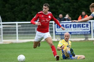 Brackley Town's Matt Lowe skips past Warrington Town's David Raven at St James Park. Photo: Steve Prouse