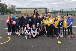 England international Serena Guthrie, back row, centre, visiting with youngsters from the Berko Belles team recently.