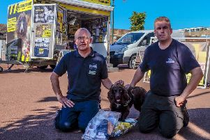 Roger Cohen with Stu Phillips, from BWY Canine Ltd, provider of the sniffer dogs, and Yoyo with tobacco seized from a shop in Bexhill