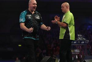 Rob Cross celebrates his magnificent victory as Michael van Gerwen graciously applauds in the background. Picture courtesy Lawrence Lustig/PDC
