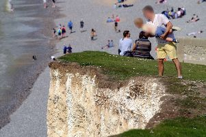 The man held his son over the steep cliff edge. Photograph by Peter Cripps