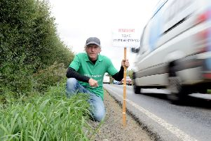 Giles Binyon on Pagham Road with one an example of one of his survey signs. Photograph: Kate Shemilt/ ks180460-2