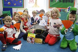Younger children at Westbourme House explore the contents of a country-themed suitcase. Spain in this case
