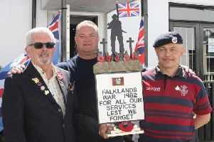 Wooden soldier statue made by Men in Sheds donated to Veterans Clubin Littlehampton and ending up at a church in the Falklands. Roy Amos presents it to Ian Neville, accomapanied by Cllr Ian Buckland. Photo by Derek Martin Photography.