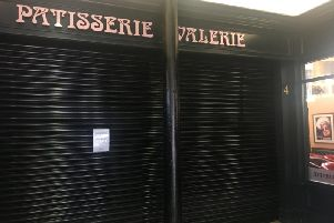 The shutter on the front of the shop has been pulled down.