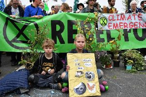 Children sit down at a blockade on Waterloo Bridge during the second day of a coordinated protest by the Extinction Rebellion group
