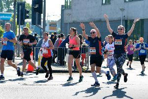 Runners raise a smile and wave for the crowd