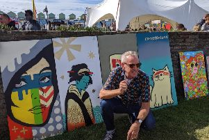DJ Fatboy Slim with the four Cassette Lord Murals at this year's LagoonFest. Photograph: Maxine Saca McMinn