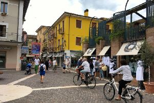 Cycling through picturesque Bardolino's old town.