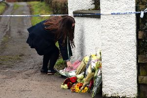 A schoolgirl adds to the floral tributes left outside the home of murder victim Robert Flowerday on Mill Road Road in Crumlin