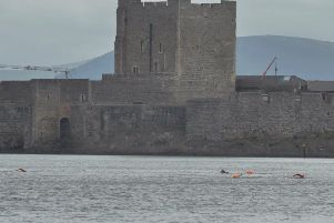 The swimmers practising for the challenge against the backdrop of Carrickfergus Castle