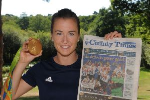 Maddie Hinch shows off her gold medal from the Rio Olympics and our sister paper the West Sussex County Times' front page. Picture by Jon Rgby