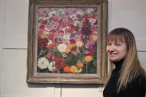 The painting by Sir Cedric Morris with auctioneer Lucy Homer
