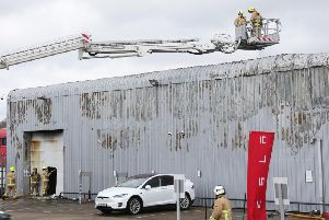 Fire crews control the fire at the Tesla dealership