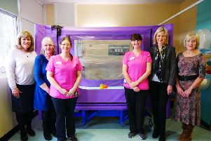 Team members from both charities presenting the bed to Howard Ward