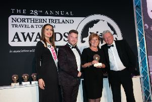 Wilma Erskine took home the NI Tourism Industry Awards 2019 at this year's Northern Ireland Travel and Tourism Awards, in association with Blue Insurance. She is pictured on stage receiving her award from Adam Bothwell of category sponsor Stena Line. Also pictured is host for the evening Charlie Lawson and ACA model Rachel Jones