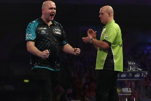 Rob Cross celebrates his momentous victory as Michael van Gerwen graciously applauds in the background. Picture courtesy Lawrence Lustig/PDC