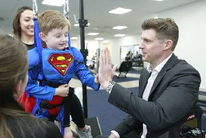 Matthew Reeve high-fiving Jasper, 5, who has greatly benefitted from treatment at Neurokinex