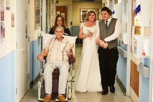 Samantha Oates is walked down the aisle on Fisbourne ward by her father-in-law Peter and son Steven - Picture by Tobias Key Photography