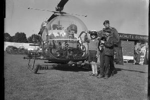 Two young pilots (and a puppy ) pose next to an army helicopter at the Northampton Show, August 5, 1966