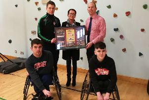 Dylan's mum, Nina Wade ( back centre) receives a presentation from St Joseph's teachers Emmett McGinty and Graeme Doherty. Pictured front, in their race chairs are James Divin (left) and Dylan (right).