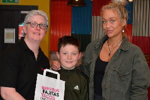 Paula Toner, manager of Boojum Restrurant, presents Long Tower Primary School pupil, T�irnan McCready, aged nine, with a voucher for one year of free food from the local Strand Road restaurant. Included in the picture is T�irnan�'s mum C�ire