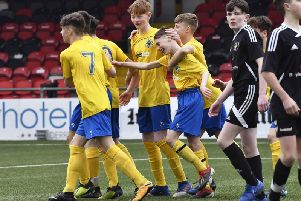St. Columb's College under-14's forward Conor Barr is mobbed by his team-mates after he had opening the scoring against Holy Cross College, Strabane. DER1519-115KM