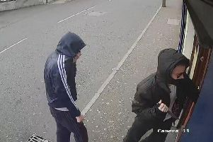 One of the culprits captured on CCTV producing a knife as he enters the premises.