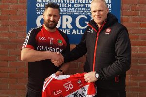 Derry senior manager Damian McErlain presents a signed Derry jersey to Sean Dolan's Games Promotion Officer, Brian O'Donnell when the Oak Leaf county team visited Creggan last week.