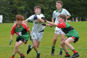 Craigbane's Blaine McDaid break through the challenge of Doire Trasna duo Conor O'Donnell and Oran Donnell at Lisnagelvin on Sunday.