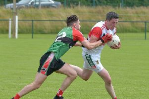 Doire Trasna's Michael Philson tackles Slaughtmanus Barry Lyons during the side's recent draw. St. Mary's are going for league glory on Friday night with Pearses trying to secure second spot ahead of Lissan. DER3219GS-002