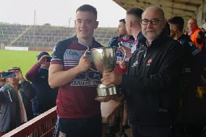 Glack captain Niall McGowan receives The Joe Brolly Memorial Cup from Derry County Chairman, Brian Smith at Celtic Park on Saturday.